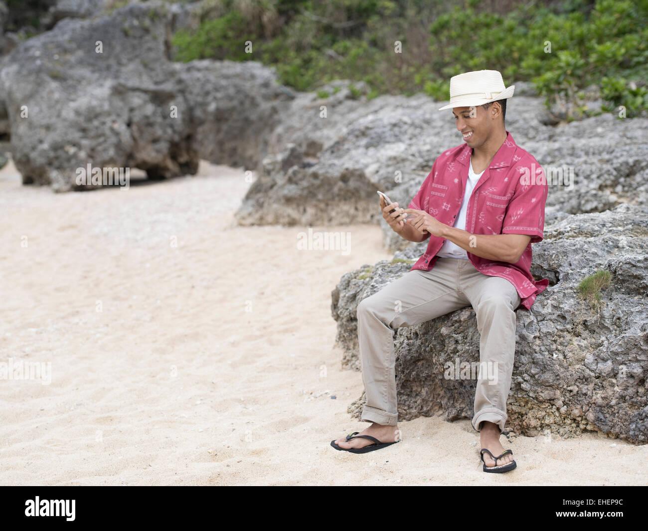 Man texting / checking internet on Apple iphone 6 smartphone while at the beach - Stock Image