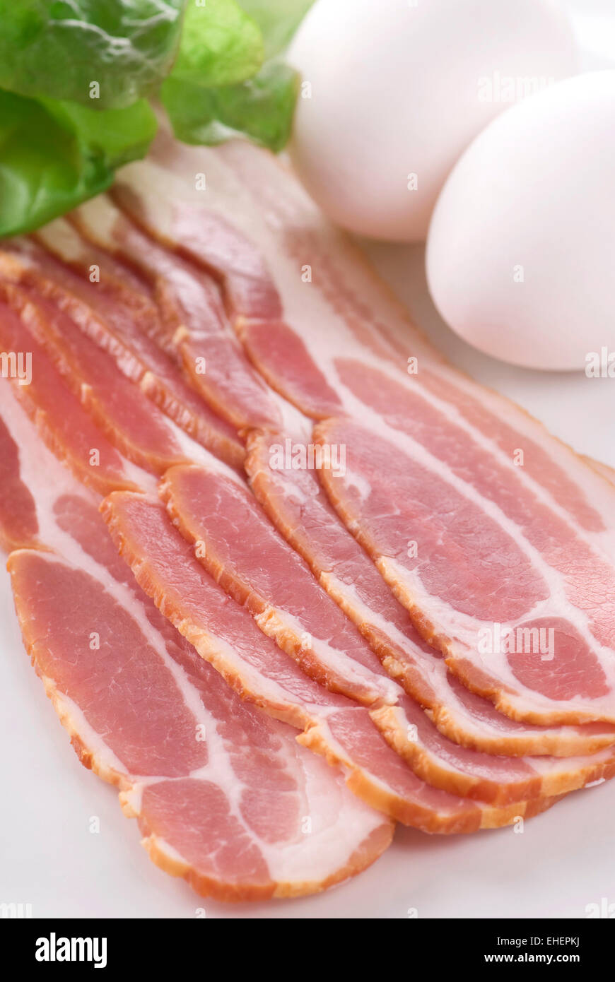 A plate with raw bacon eggs and lettuce. - Stock Image