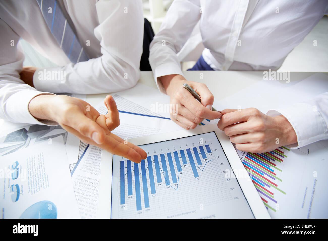 Businesspeople analyzing statistics - Stock Image