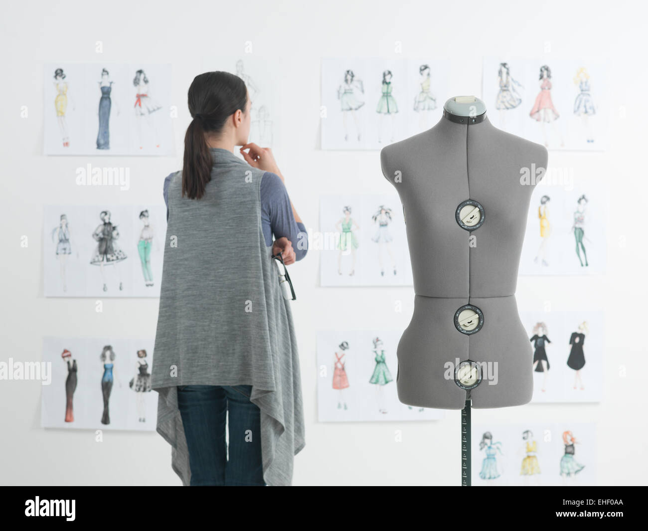 successful female fashion designer looking at drawings in her studio - Stock Image