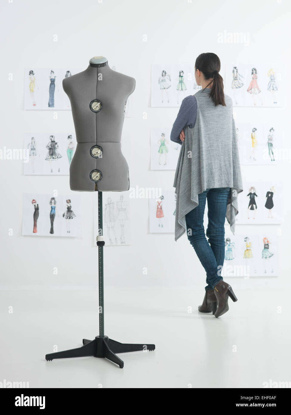 female fashion designer standing in her studio looking at sketches - Stock Image