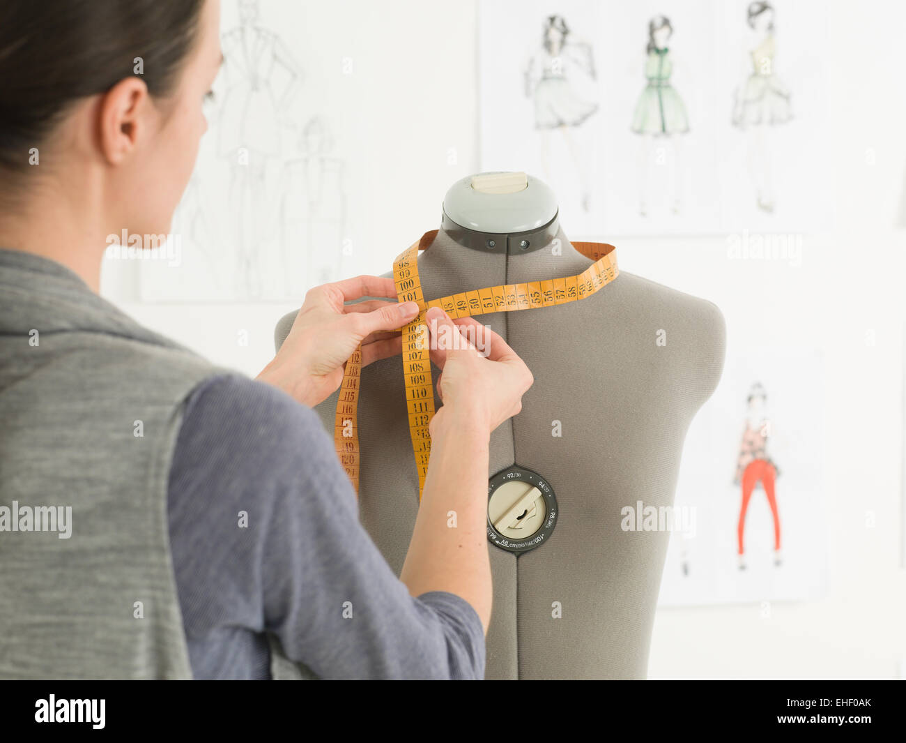 closeup of fashion designer measuring neck of dummy in a studio - Stock Image