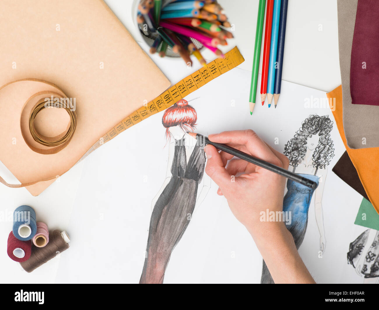 female hand drawing fashion sketch on desk with designing equipment - Stock Image