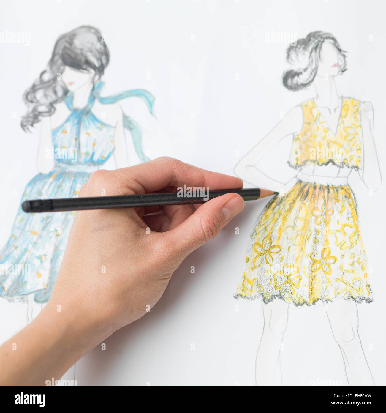 closeup of human hand drawing fashion design on paper - Stock Image
