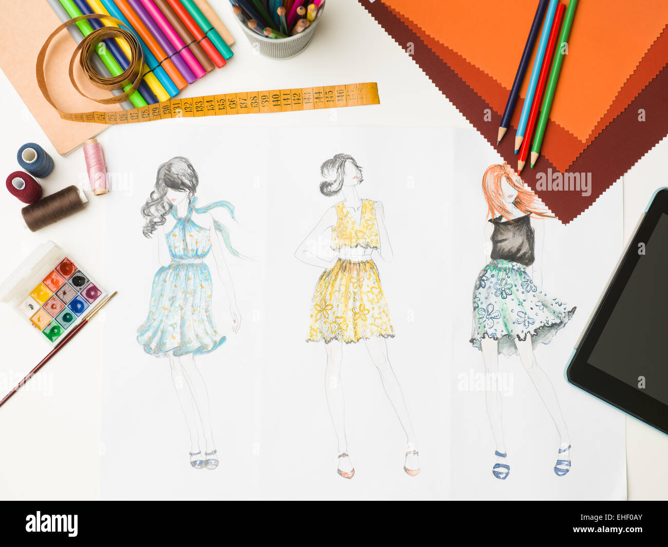top view of desk with fashion designing equipment and sketches - Stock Image