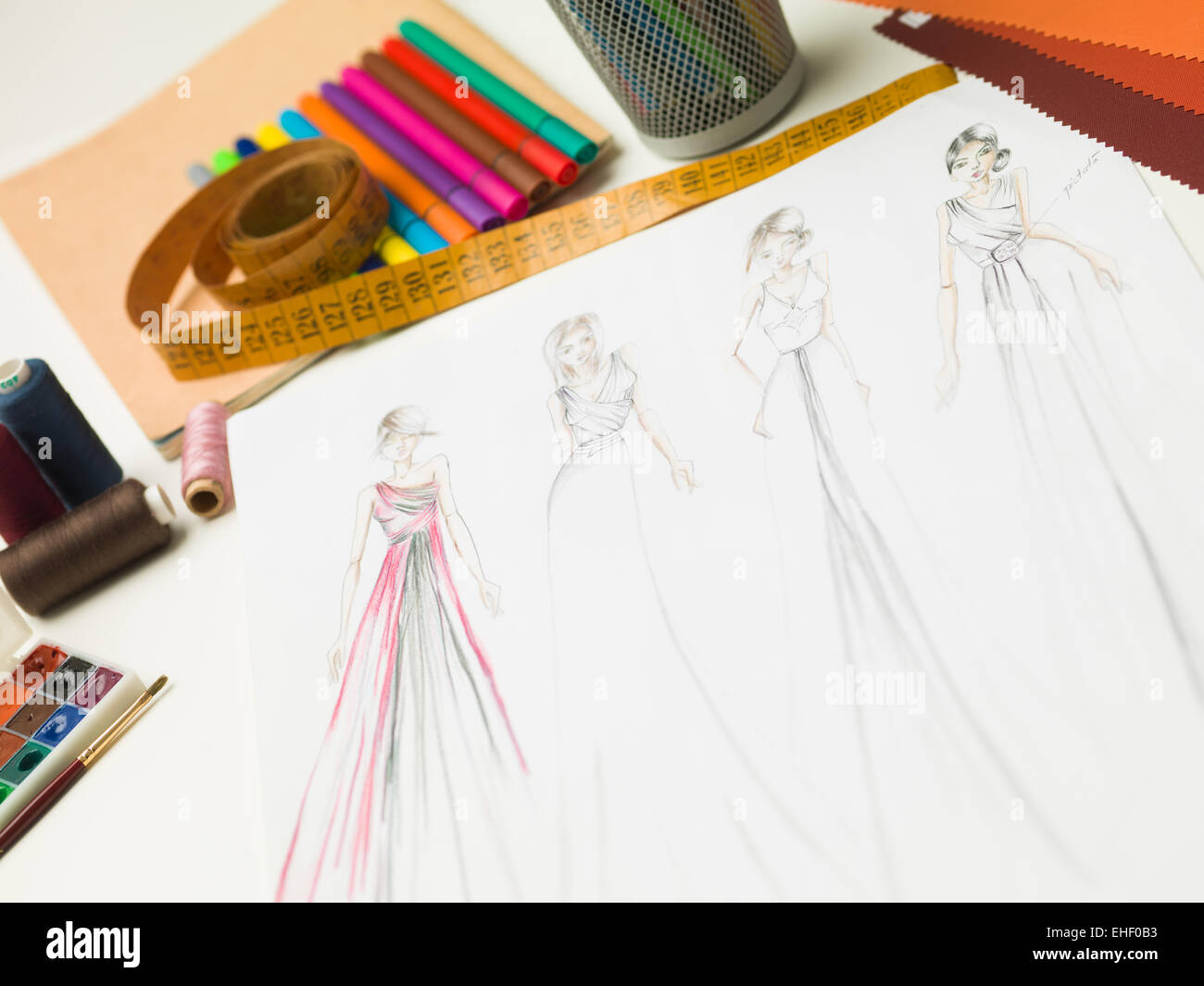 closeup of fashion designer workspace with sketches of evening gowns and designing equipment - Stock Image