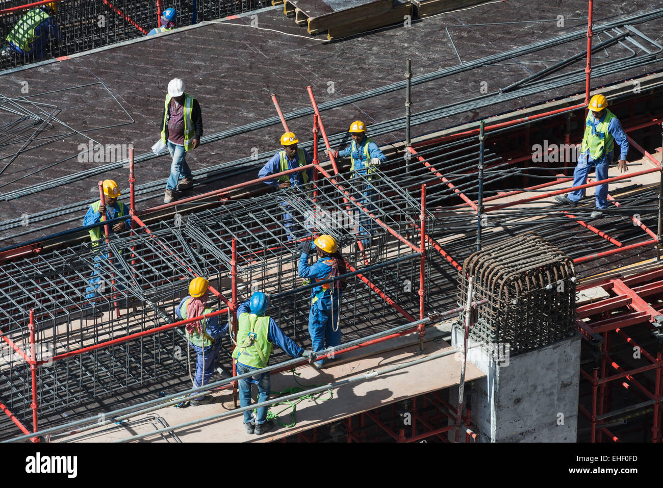 Migrant workers on construction site of high-rise  apartment skyscraper tower in Dubai United Arab Emirates - Stock Image