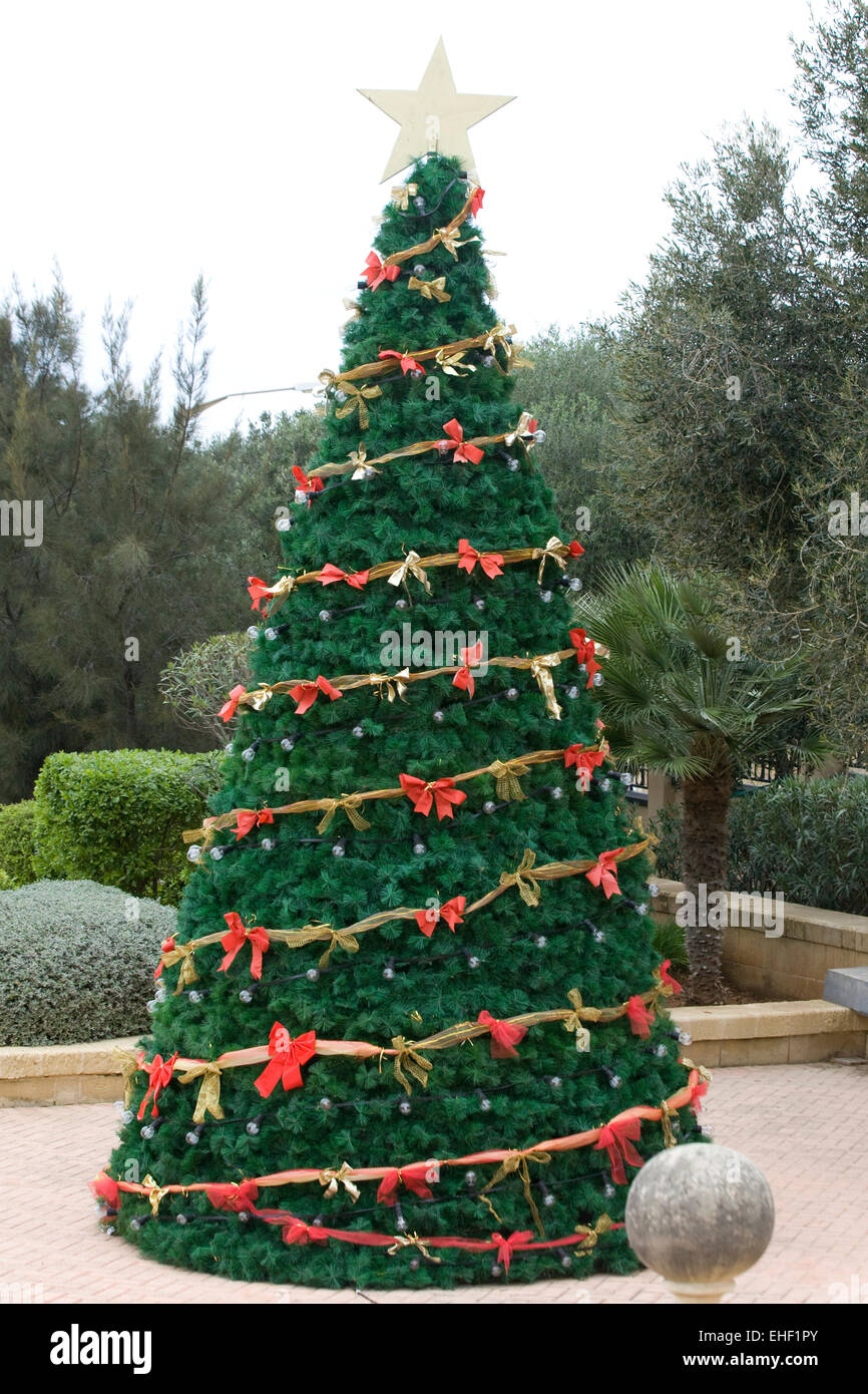 real christmas tree decorated with red bows and fairy lights with a christmas star on the