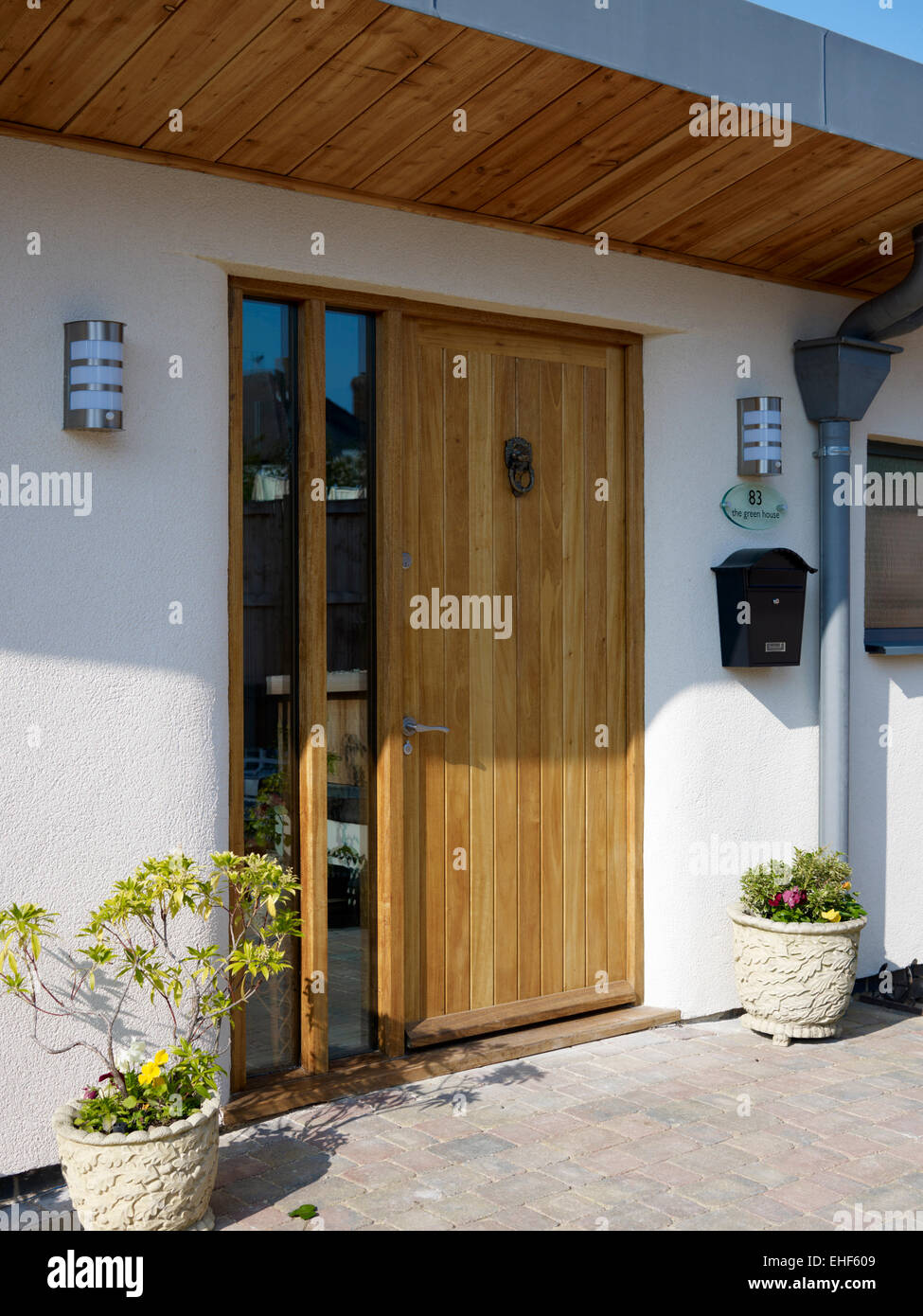 Pine Front Door With A Pair Of Planters And Matching Wall Lights In