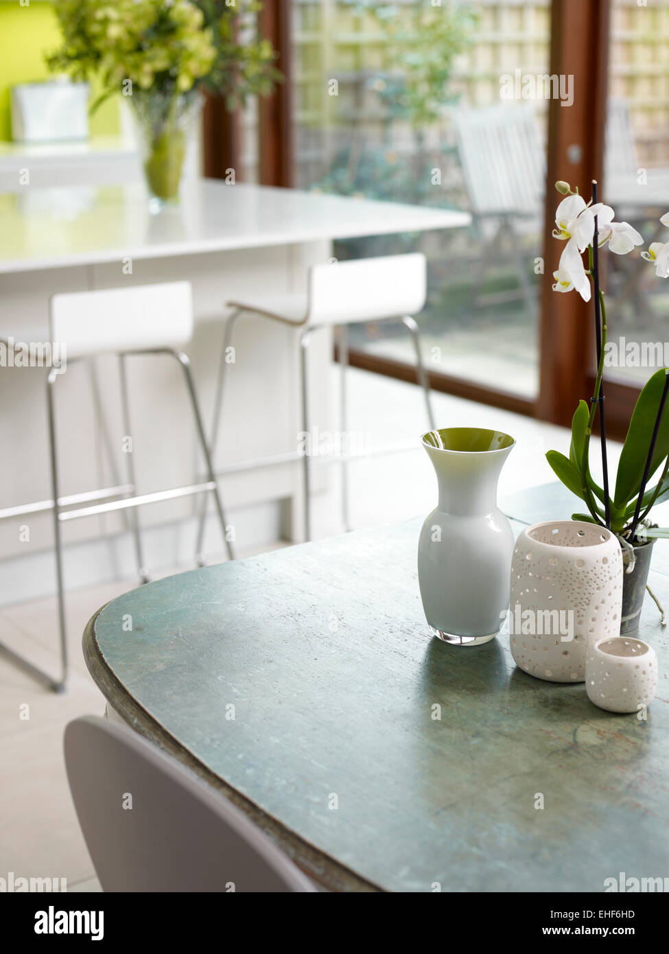 Close up of a small orchid, vases and candle holders in Streathbourne Road home, UK - Stock Image