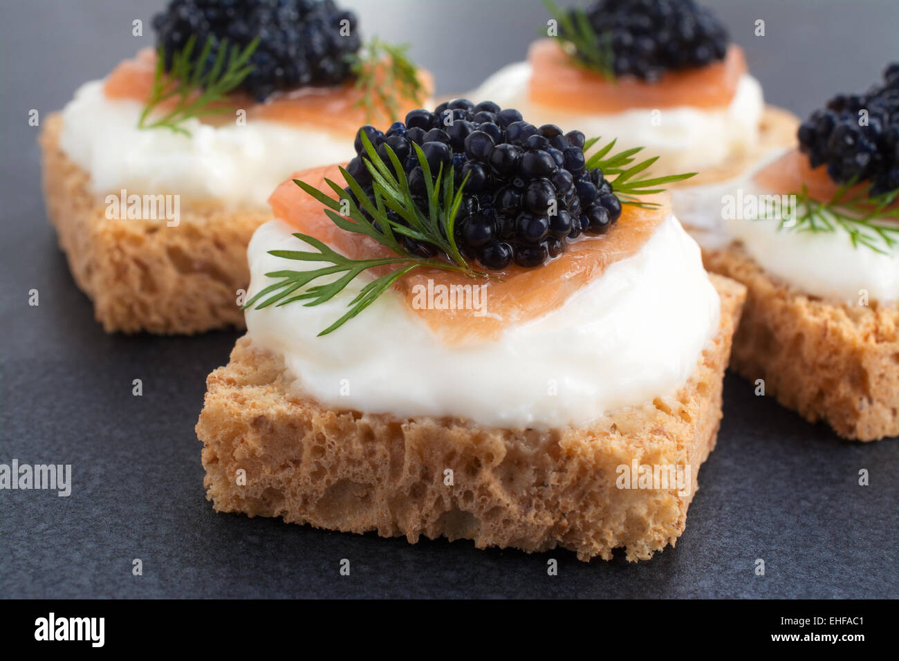Canapé of Caviar on top of salmon with cream cheese, room for text - Stock Image
