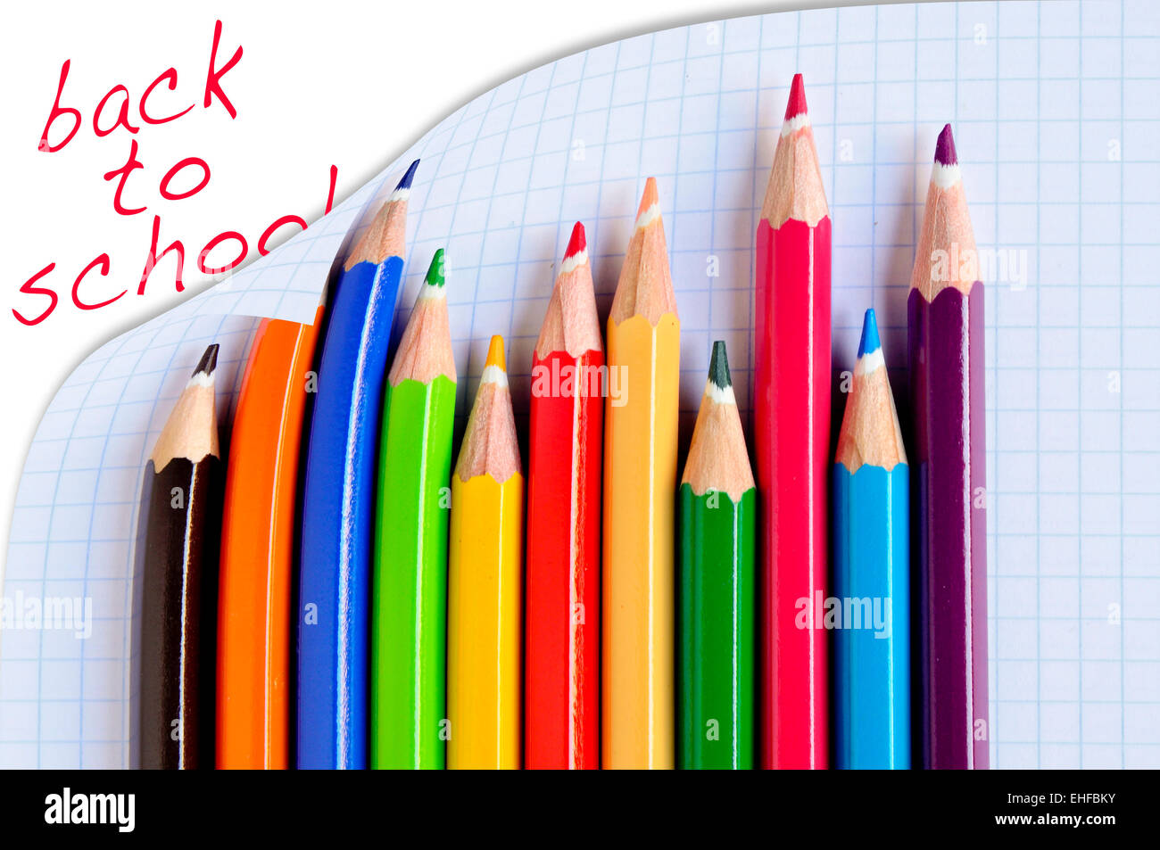 sentence back to school and some pencil crayons of different colors on a checkered paper sheet - Stock Image