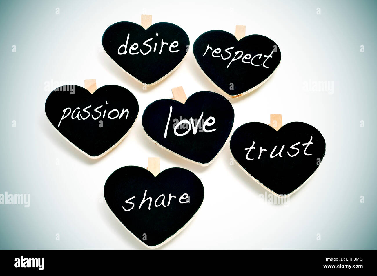 some heart-shaped blackboards with different words written on them related to love concept, such as respect, trust - Stock Image