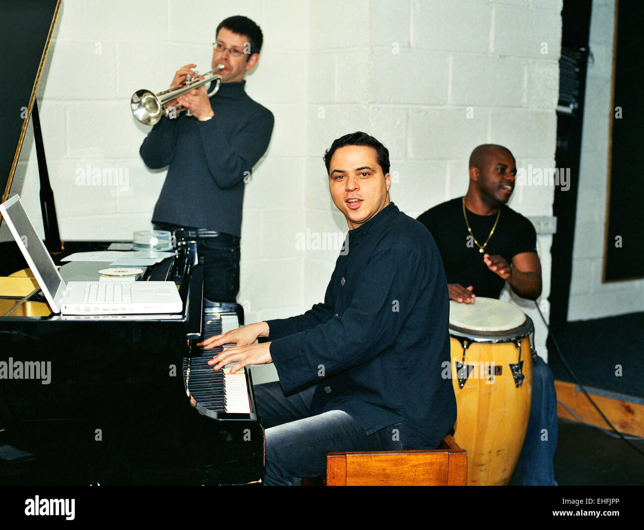 Alex Wilson on piano with Emeris Solis on congos and Paul Jayasinha on trumpet. - Stock Image