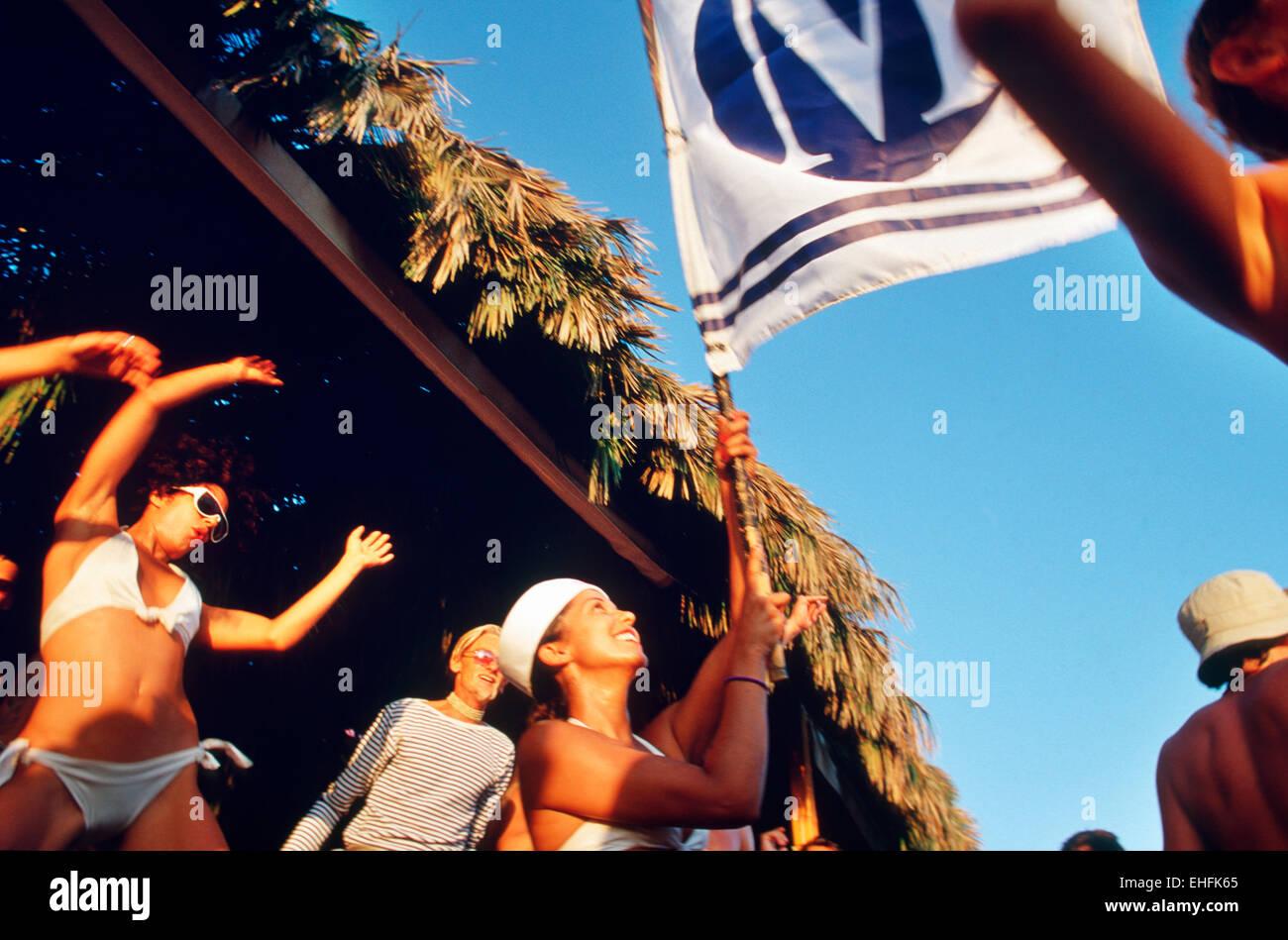 Girls dancing on Sa Trinchas beach Ibiza. - Stock Image
