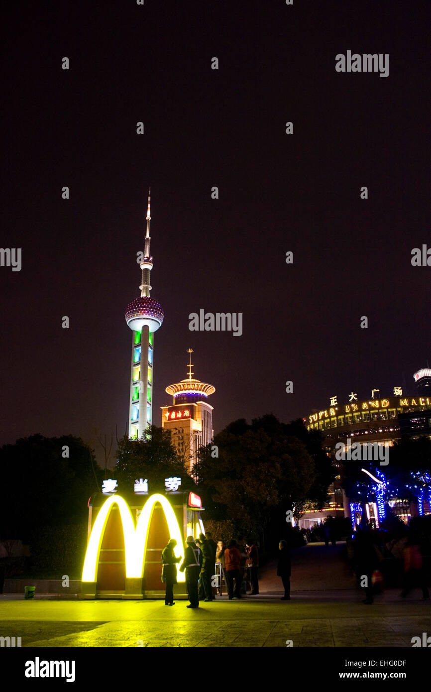 The Oriental Pearl TV tower appears from behind a MacDonalds sign Shangai. - Stock Image