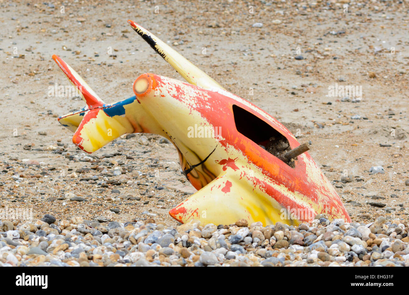 Part of a fairground ride wedged into the shingle on a beach. - Stock Image