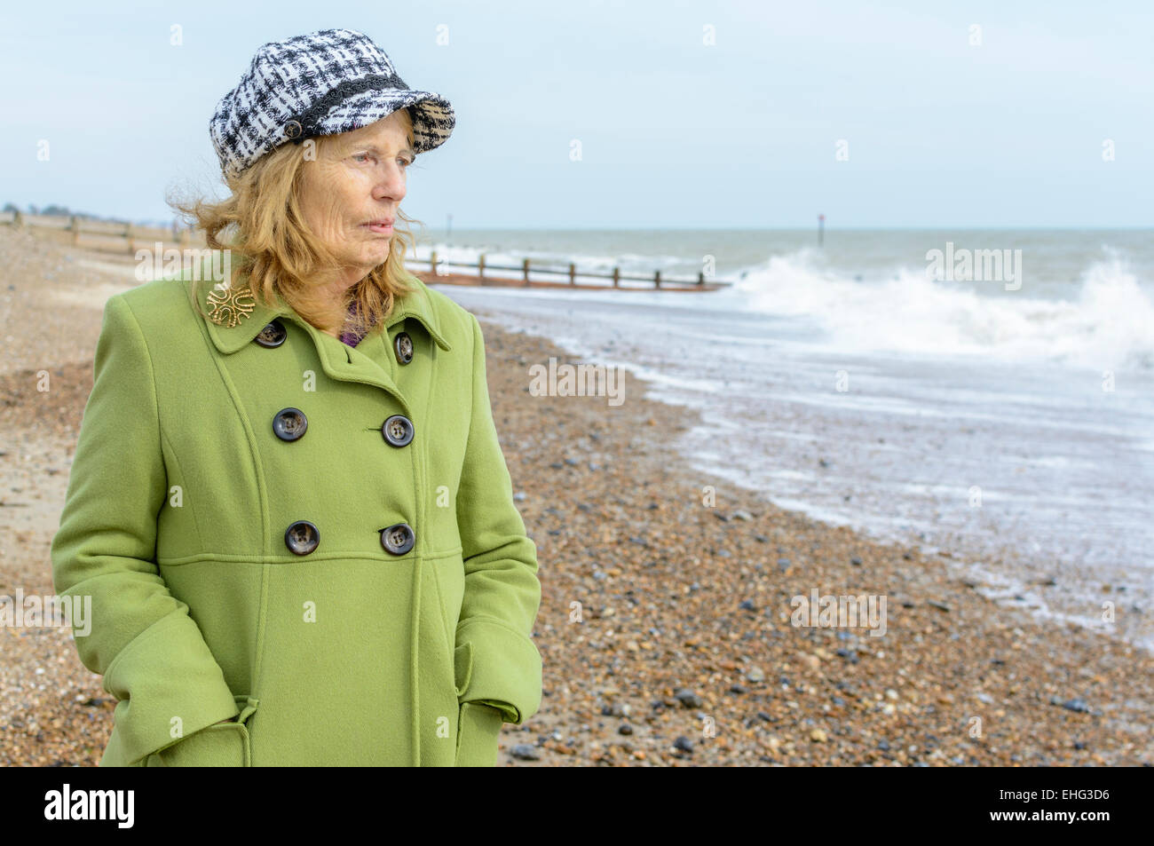 Elderly woman dressed warmly in the cold on a beach, looking out to sea. - Stock Image