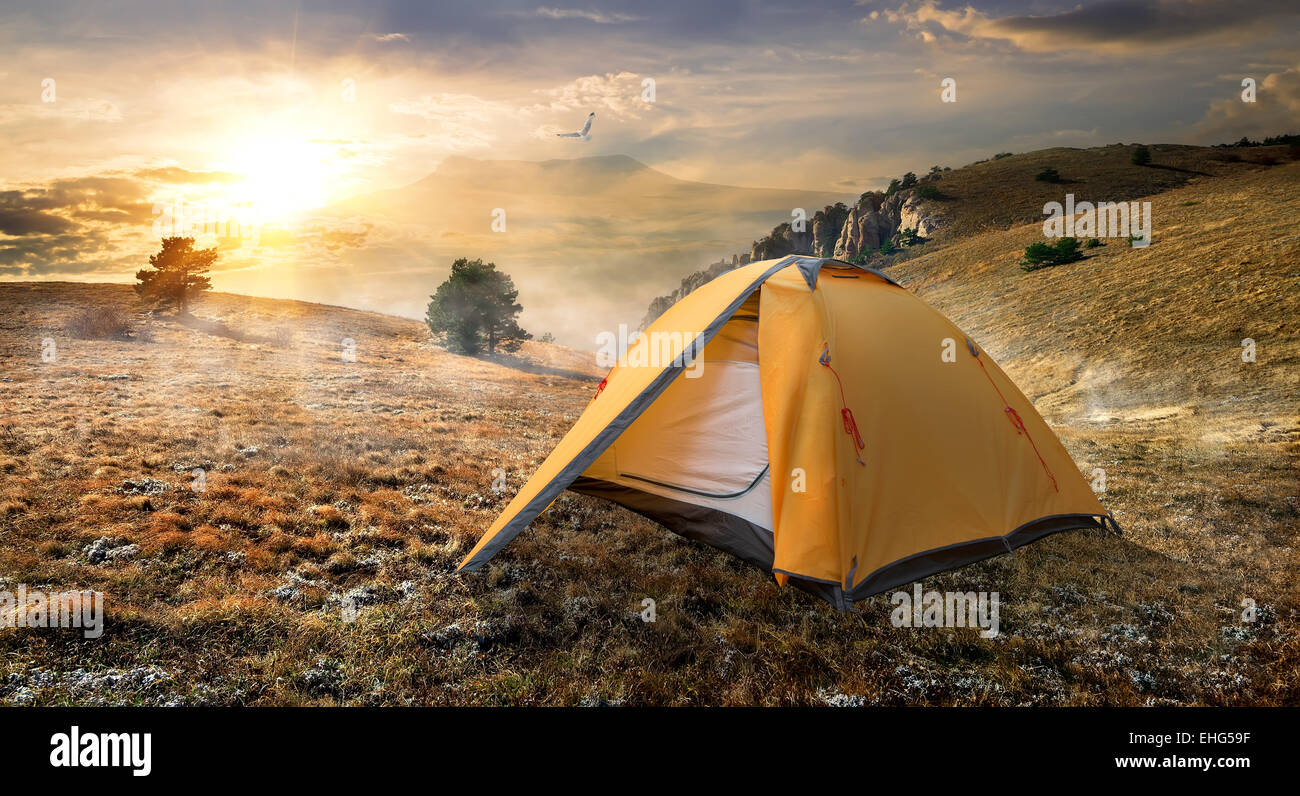 Tourist tent in autumn mountains at sunrise - Stock Image