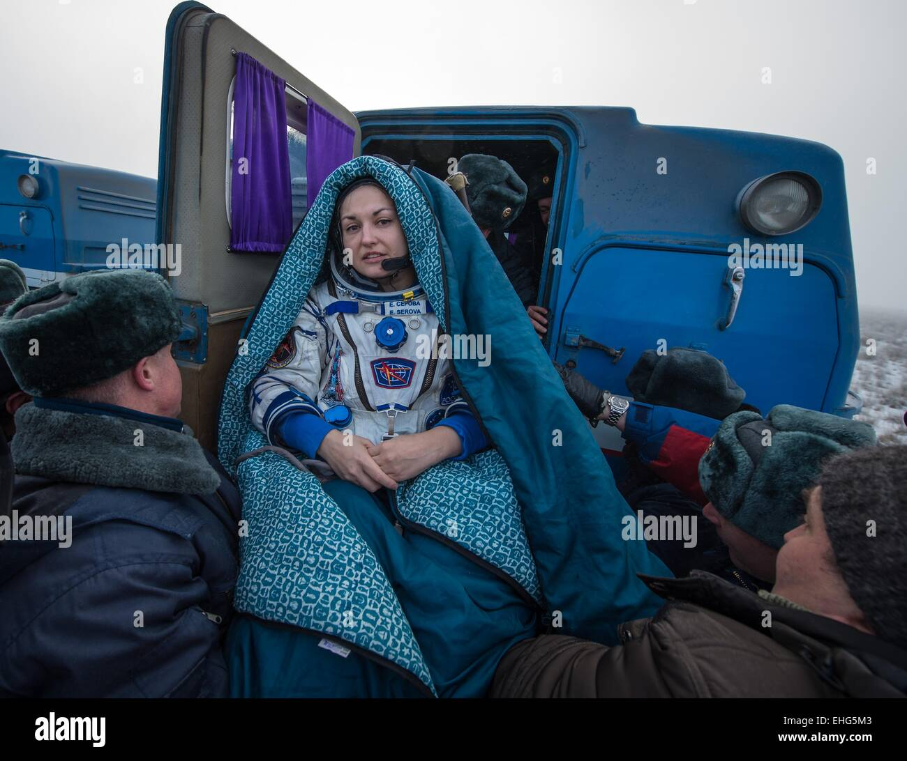 ISS Expedition 42 Cosmonaut Elena Serova wrapped in a blanket is carried to the recover vehicle outside the Soyuz - Stock Image