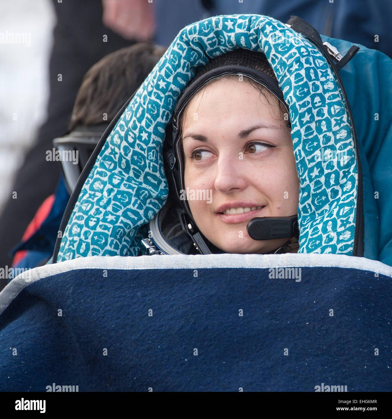 ISS Expedition 42 Cosmonaut Elena Serova wrapped in a blanket outside the Soyuz TMA-14M  capsule just minutes landing - Stock Image