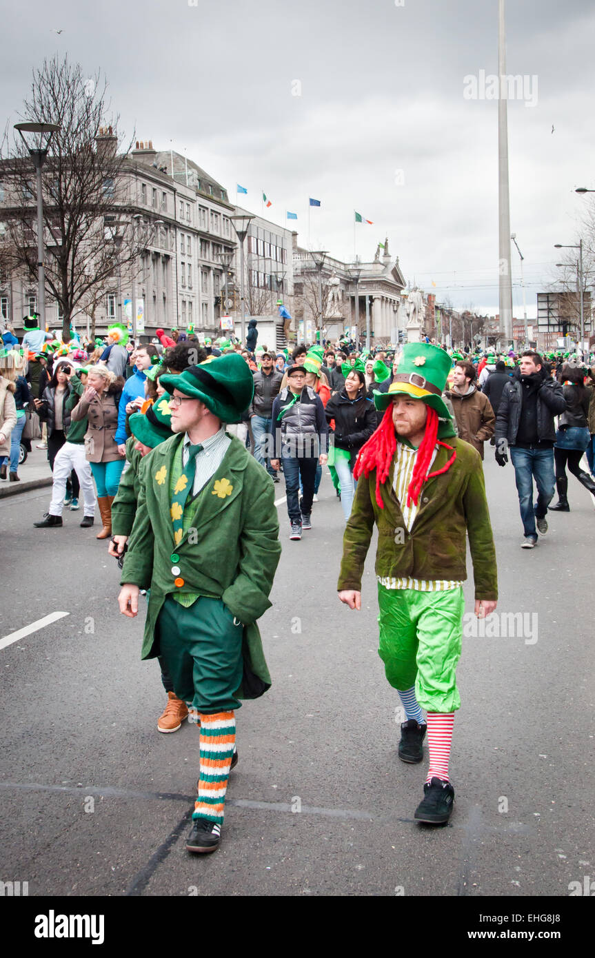 Three men wearing Leprechaun hats and clothing walk down O'Connell Street in Dublin during St Patrick's - Stock Image