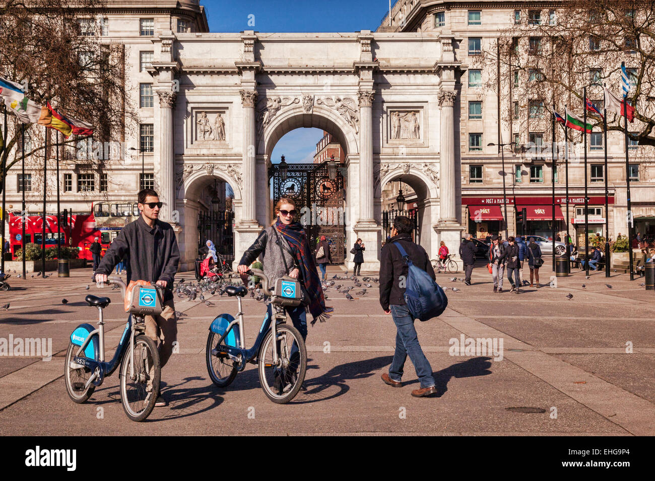 Marble Arch, London, England. Tourists walk  with hired cycles. - Stock Image