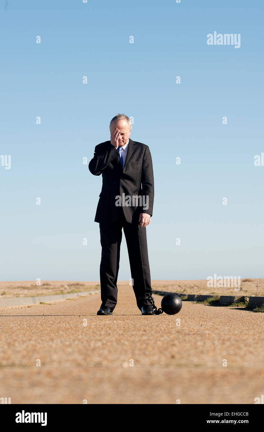 Businessman standing in the middle of a long road, head in hand and attached to a ball & chain. - Stock Image