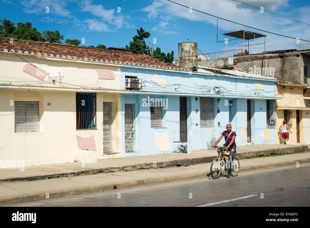Cuba Santa Clara street road scene primitive houses homes blue cream terrace cyclist bicycle - Stock Image