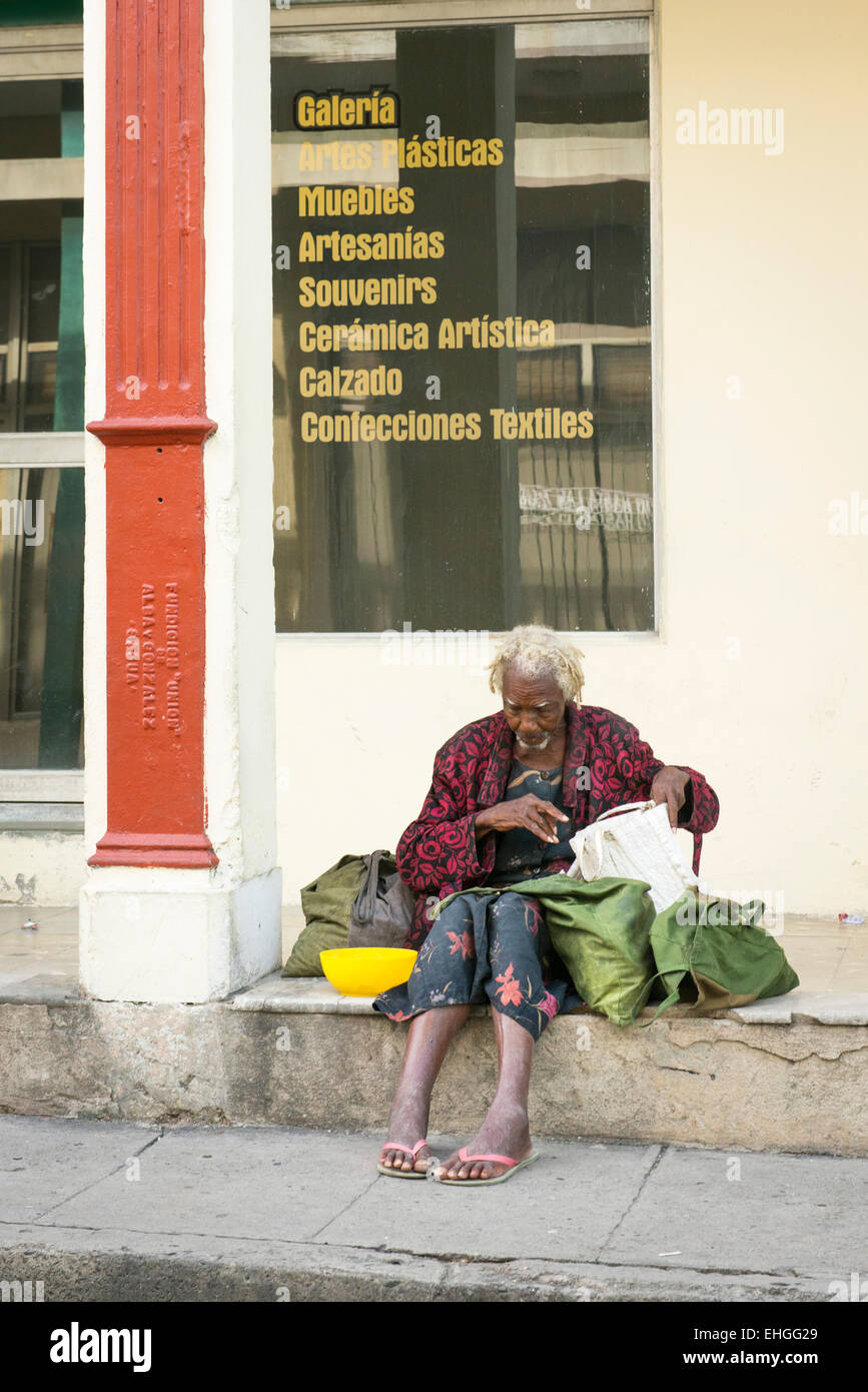 Cuba Santa Clara elderly old bag man tramp sitting on steps of furniture shop store general household goods textiles - Stock Image