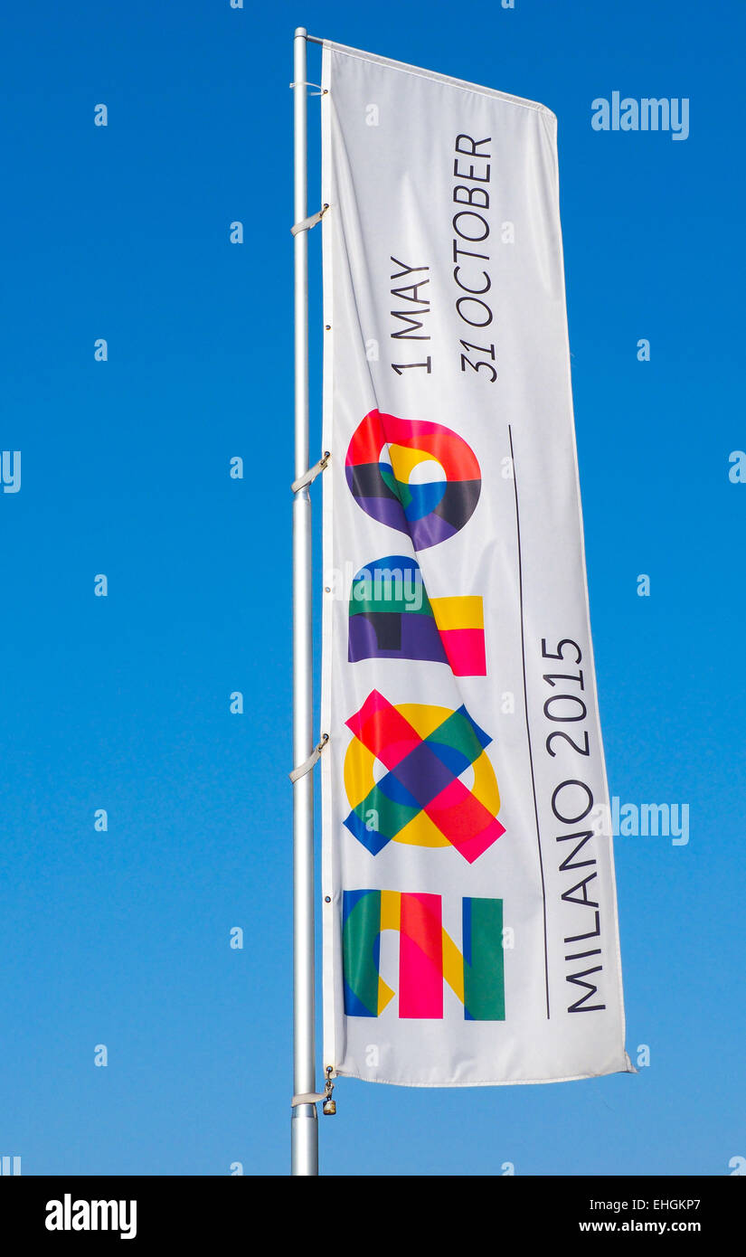Giant flag with logo of the 2015 international Milan Expo Fair dedicated to food; blue sky in the background, space - Stock Image