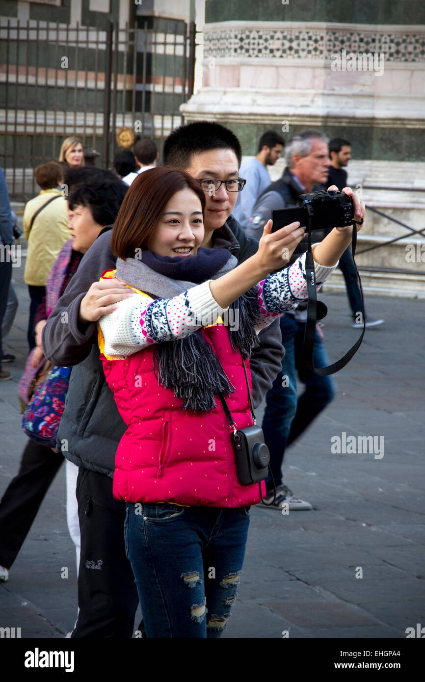 Tourists taking 'selfie' photo in front of Cathedral & Campanile, Piazza del Duomo, Florence, Tuscany, Italy Stock Photo