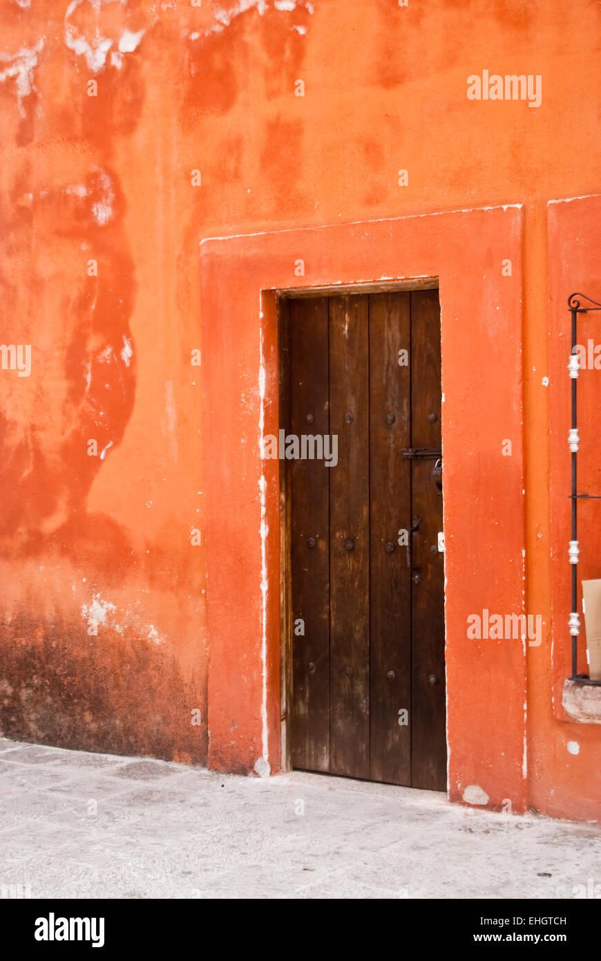 Orange adobe house with wood door Mexico - Stock Image
