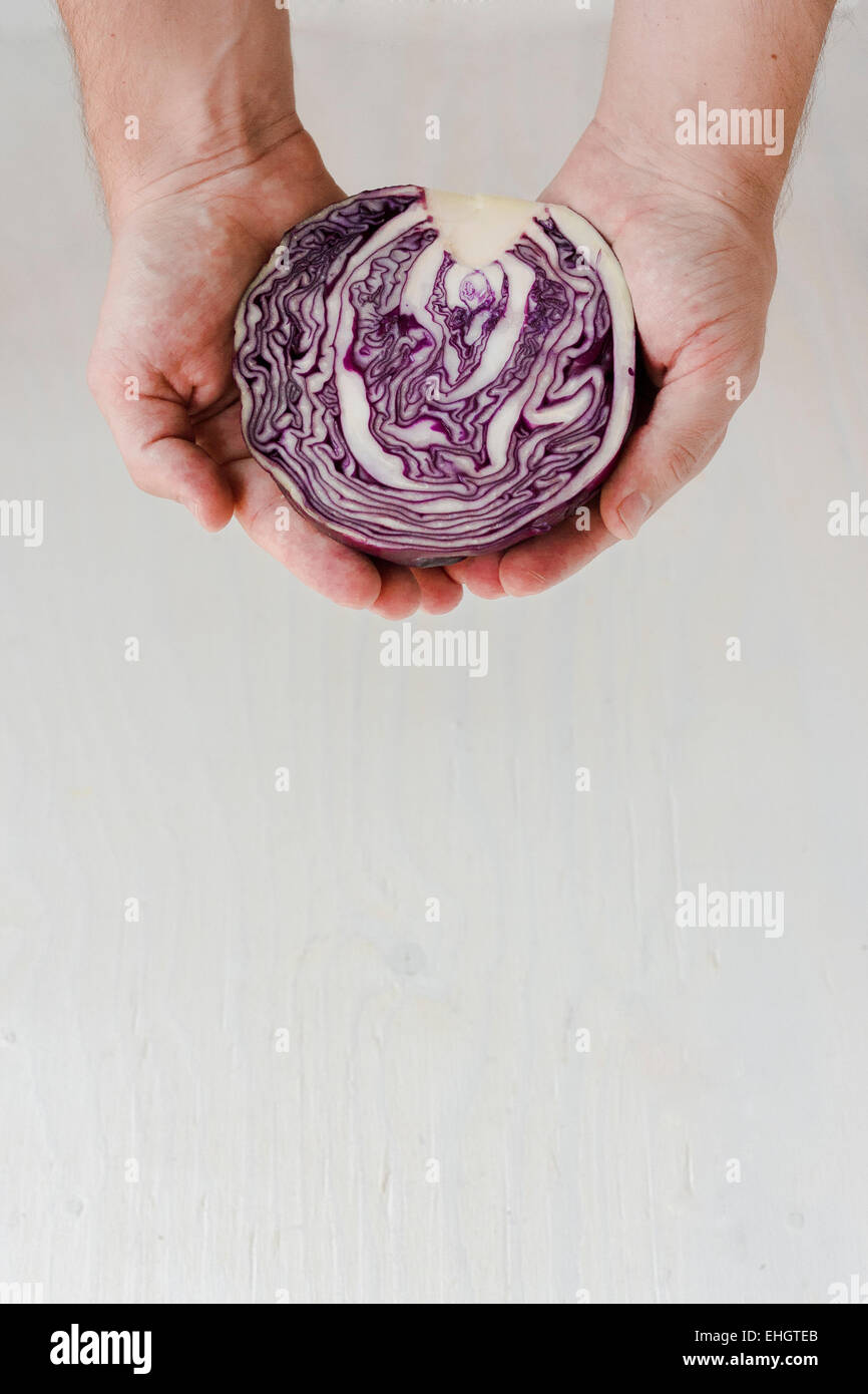 Young man holding half a red cabbage. Complexity. - Stock Image