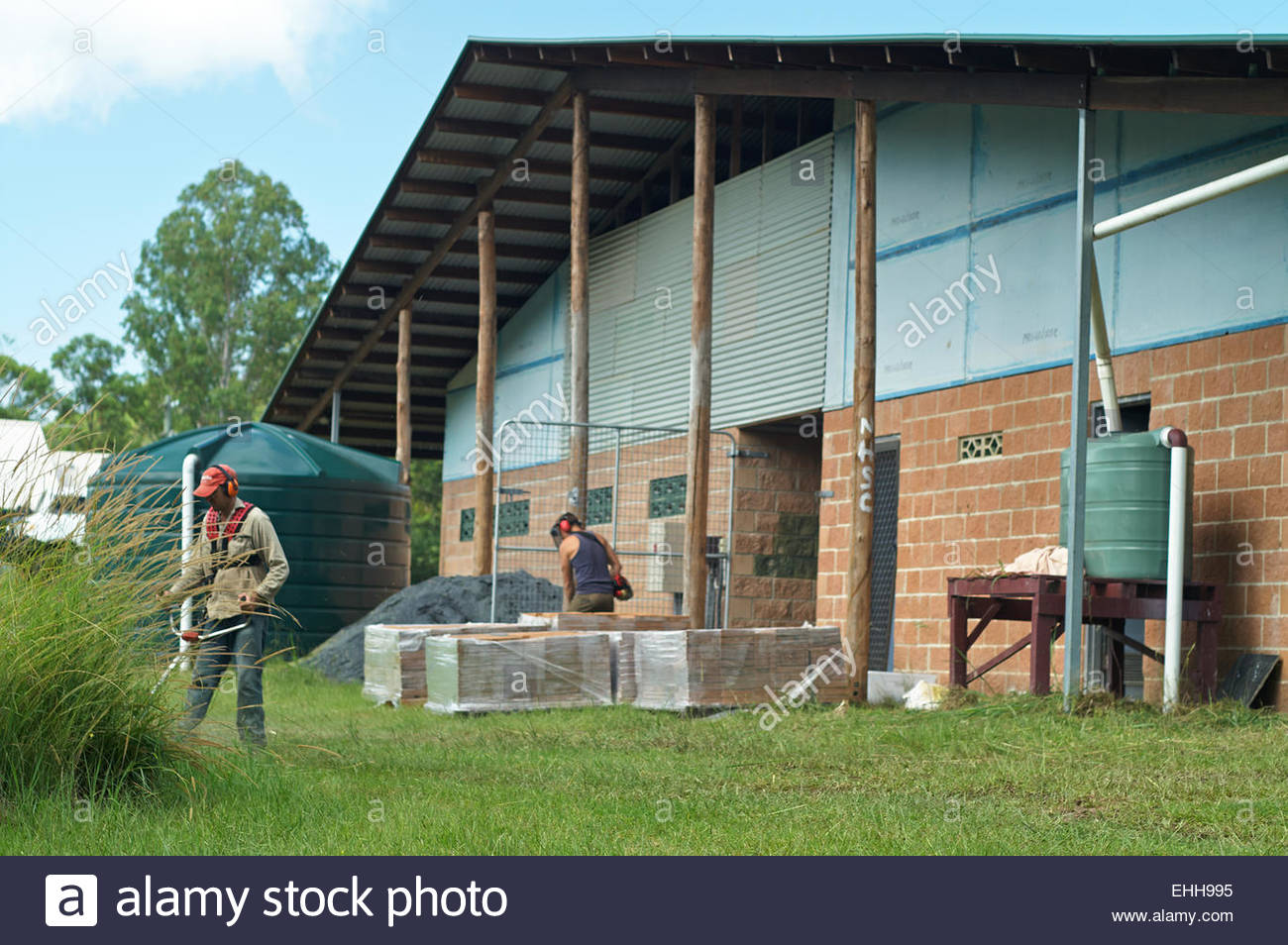 Two men cutting the grass around several pallets of pavers and two water tanks, at a working-bee for Nimbin soccer - Stock Image