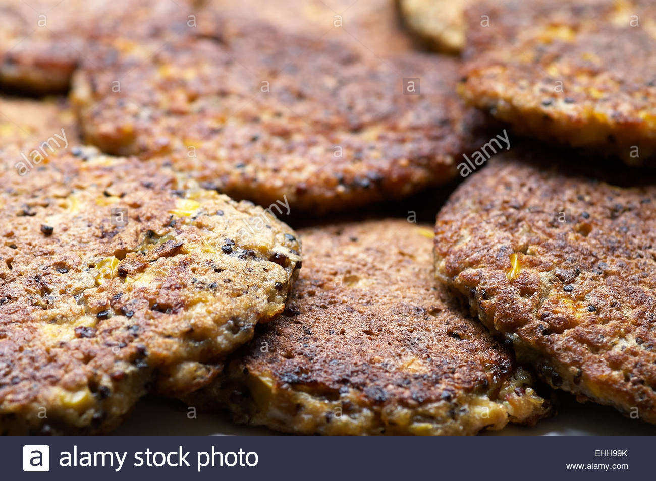 A pile of hot freshly-cooked, golden-brown, corn and quinoa fritters; ready to serve and eat - yum! Comfort food, - Stock Image