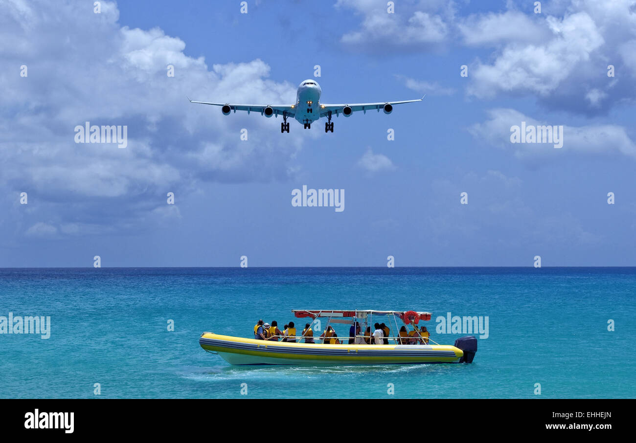 Passenger airplane overflies boat. - Stock Image