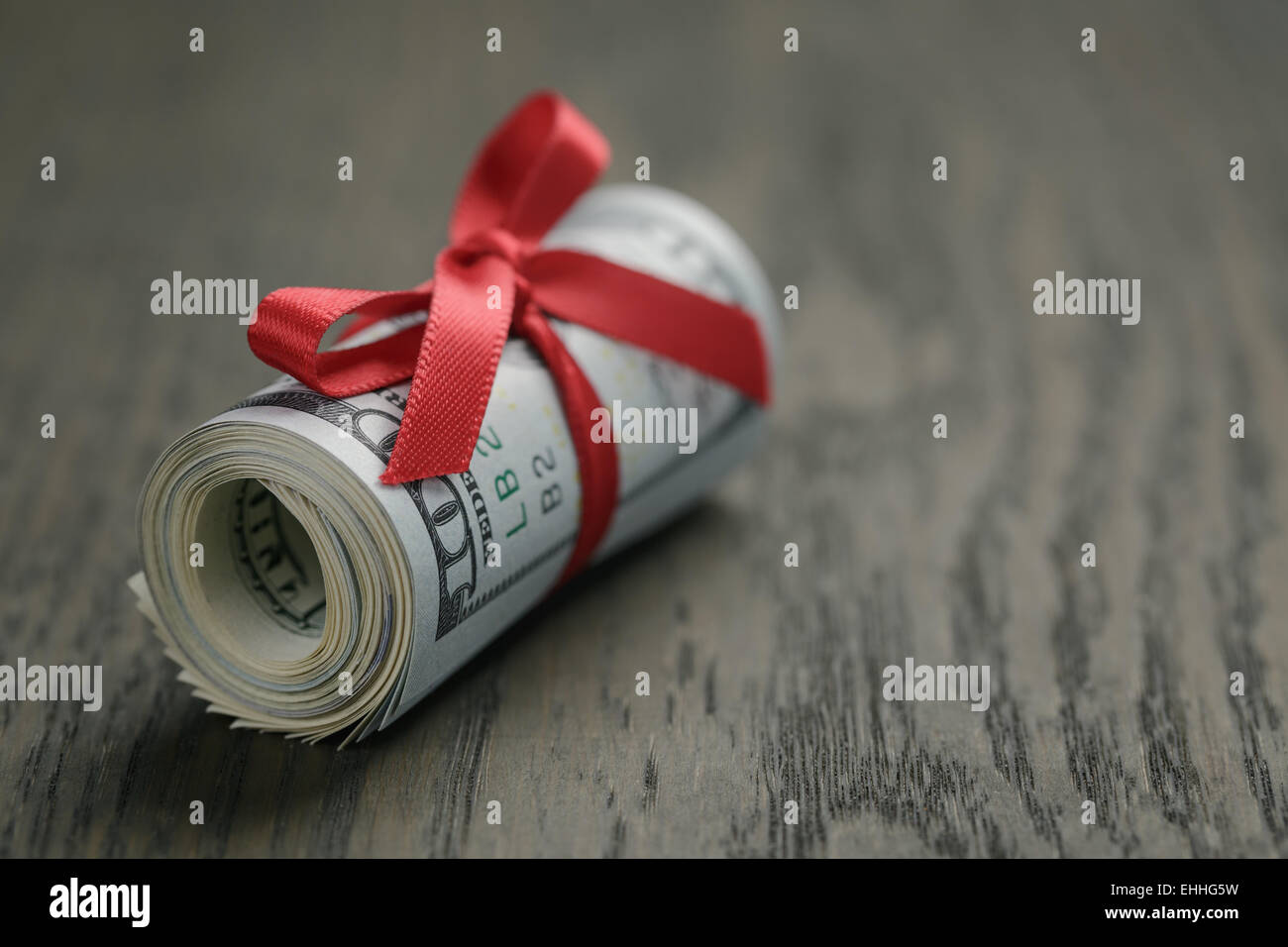 roll of hundred dollar bills on wooden table stock photo 79676517