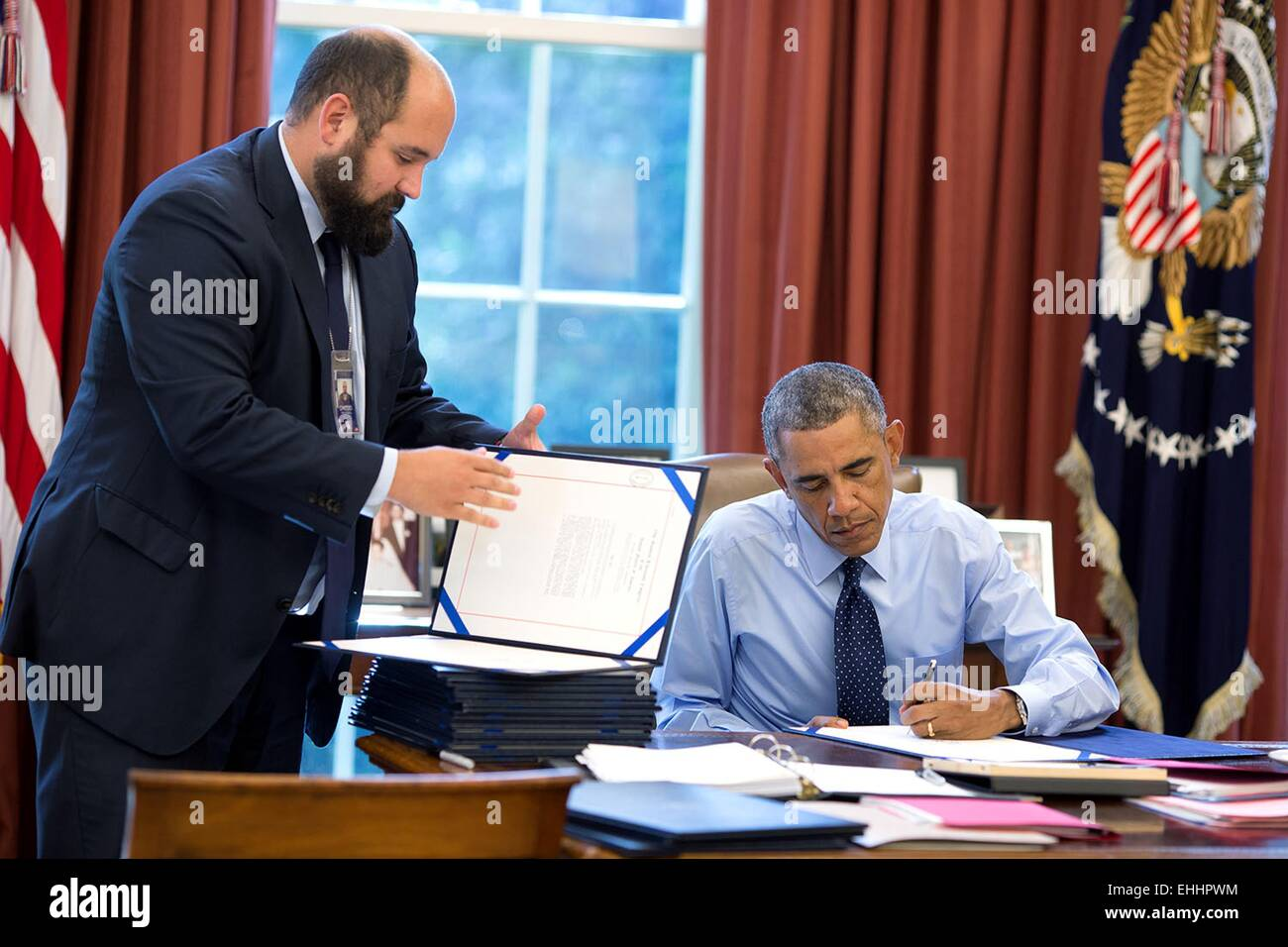 US President Barack Obama, assisted by Deputy Staff Secretary Ted Chiodo, signs bills in the Oval Office of the - Stock Image