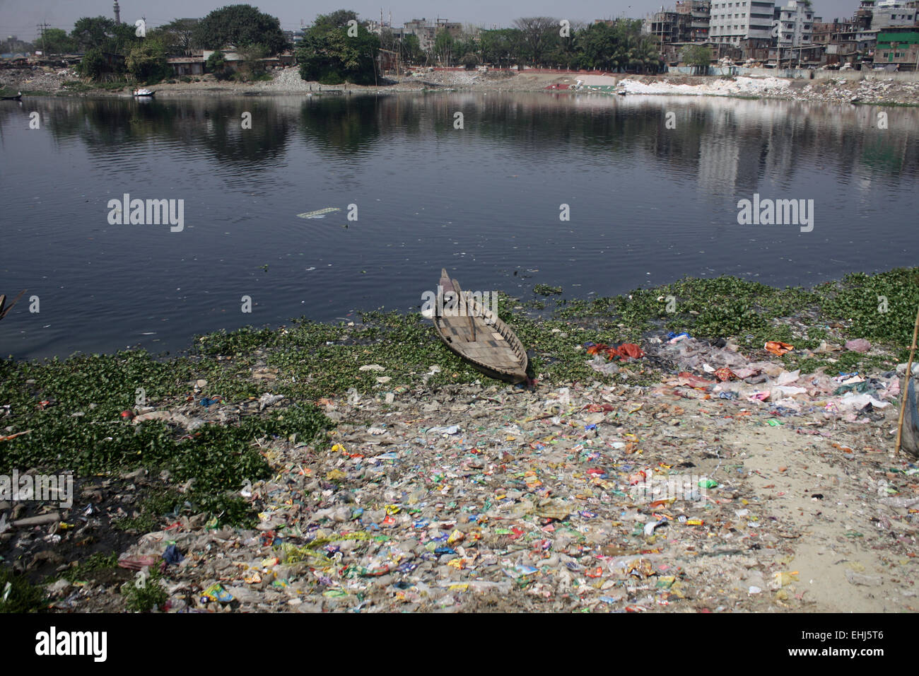 Boats in the in the polluted Buriganga River. Water pollution in the Buriganga River has reached alarming levels. - Stock Image