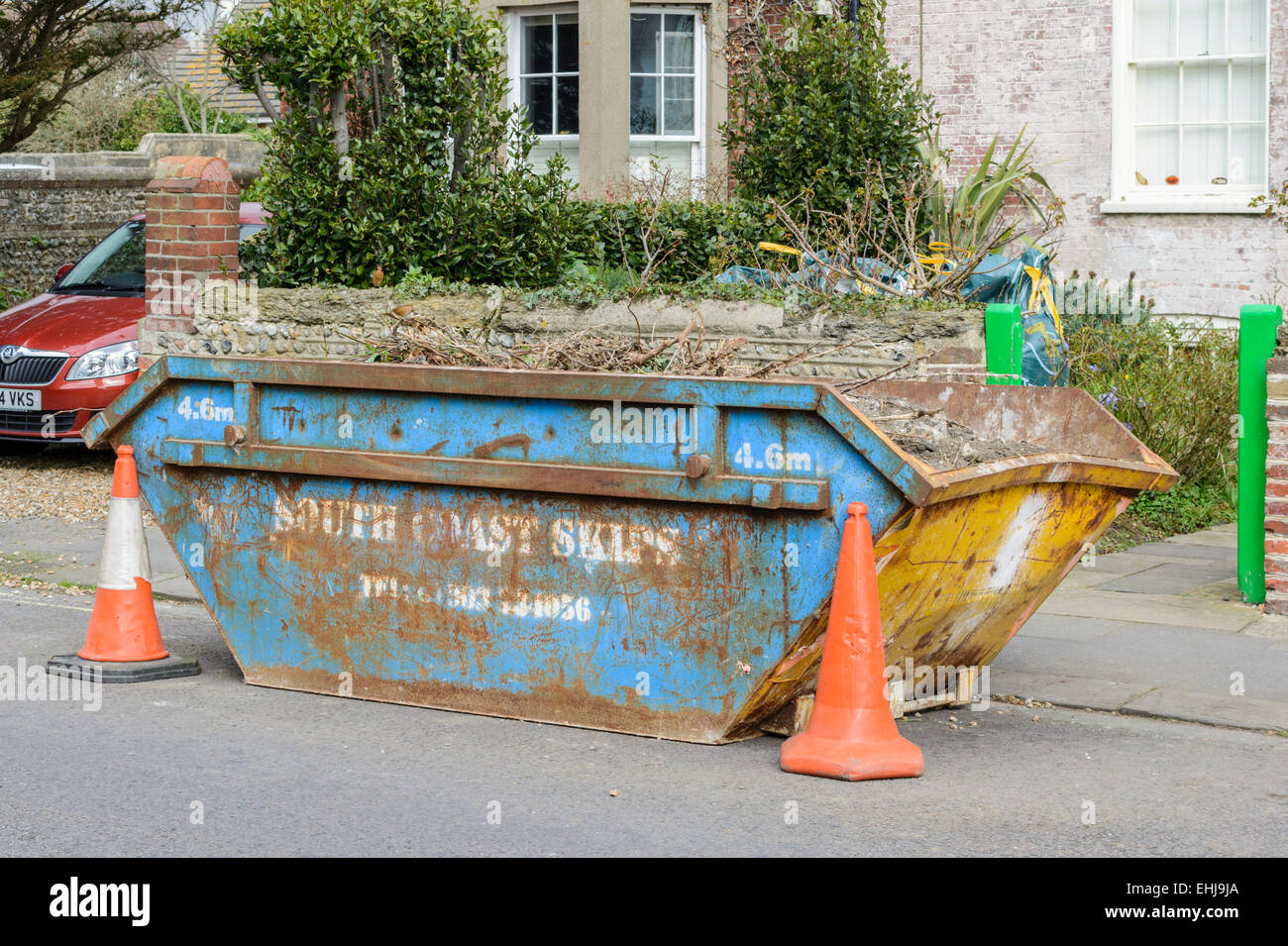 A rubbish skip parked in the road. - Stock Image