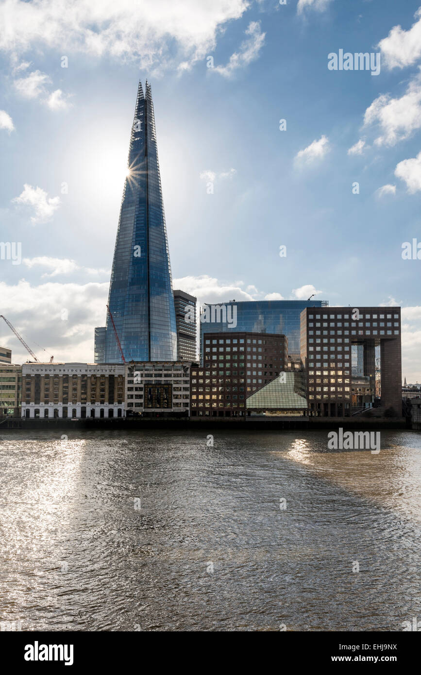 The sun shining behind the London landmark skyscraper The Shard from a cross the River Thames - Stock Image