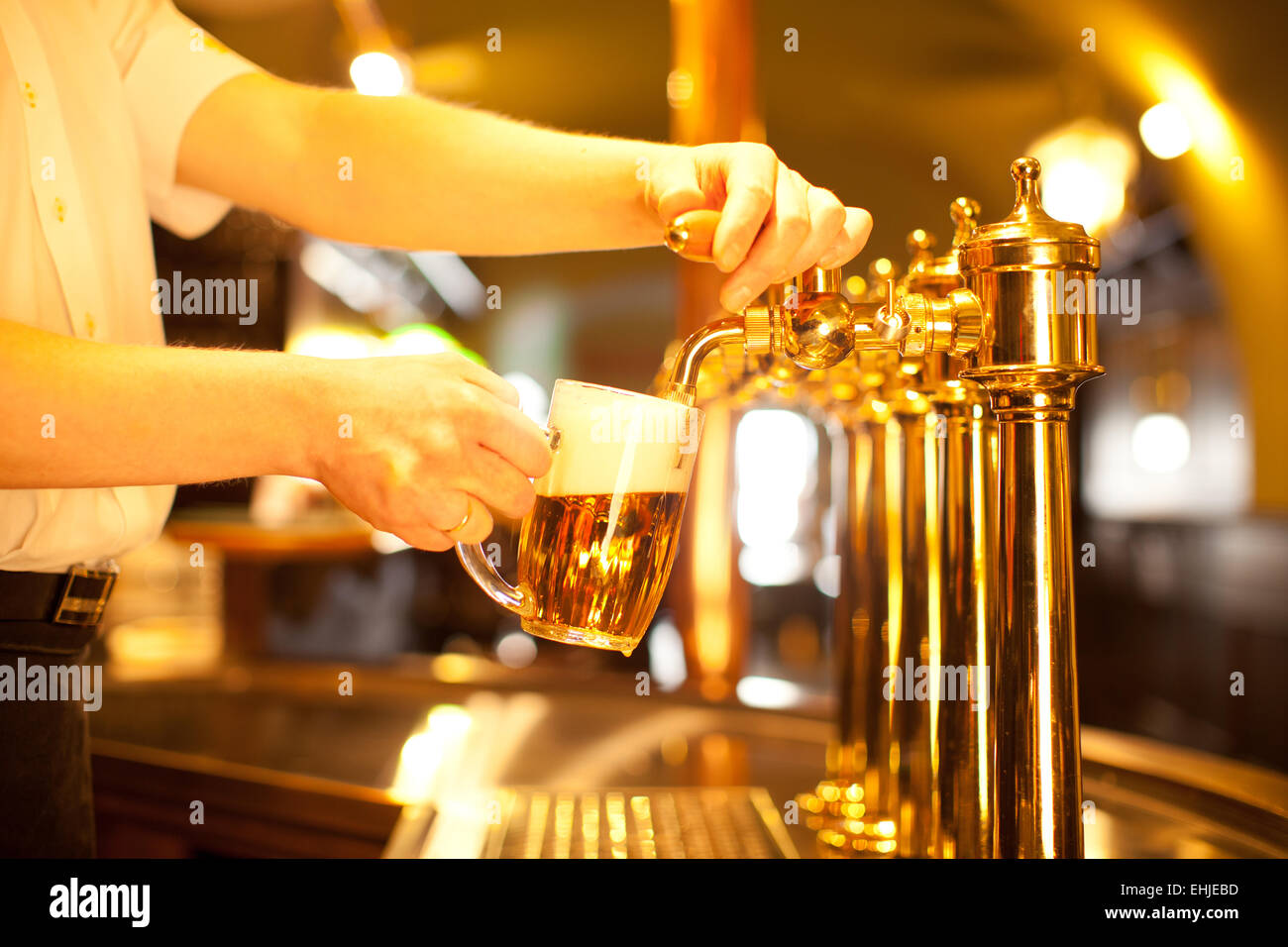 waiter is drafting a beer from a golden spigot - Stock Image