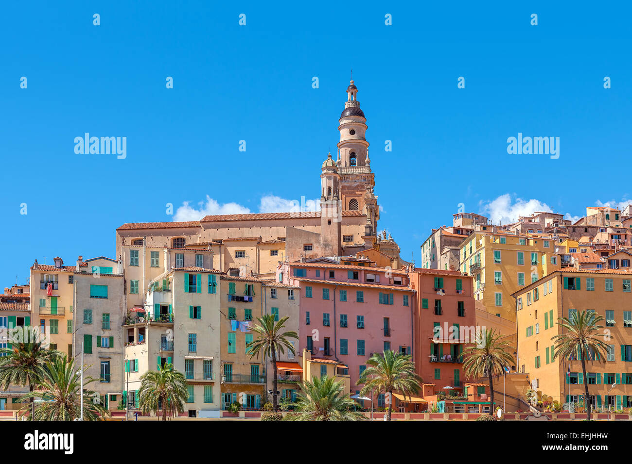 Belfry among colorful houses under blue sky in Menton - small town on French Riviera. - Stock Image