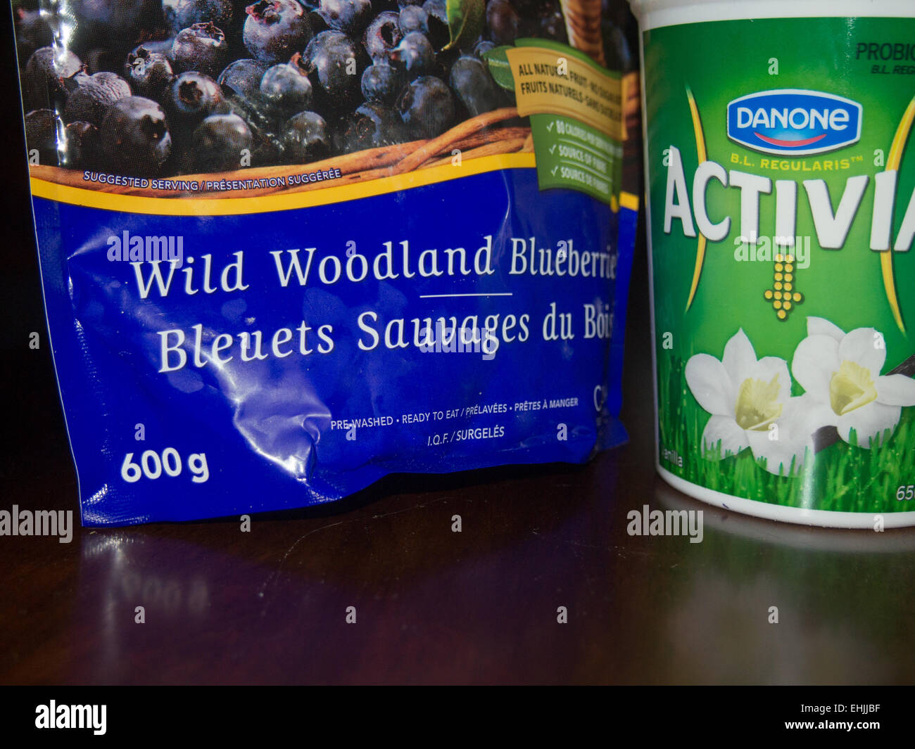 bag of wild blueberries and container of vanilla yogurt - Stock Image