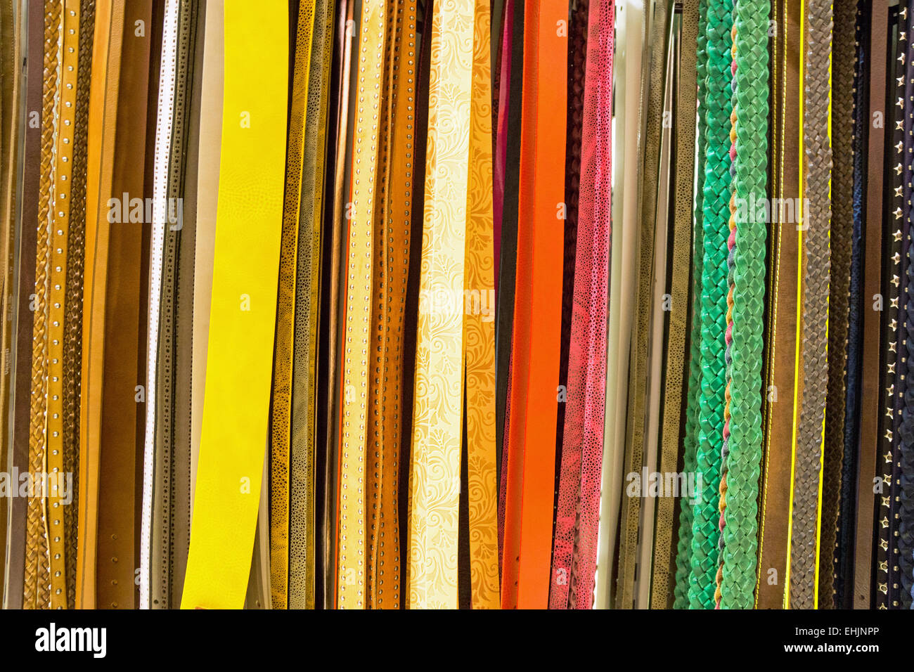 A variety of colourful belts for sale - Stock Image
