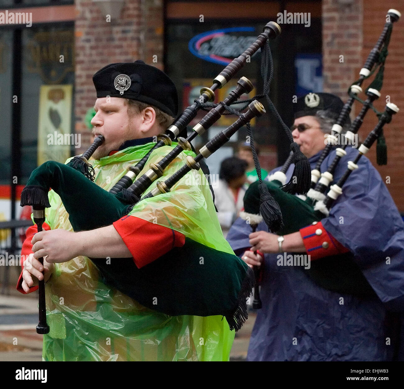 Two pipers in the William Sutherland Reid Pipes and Drums band clad in colorful rain ponchos over ancient Scottish - Stock Image