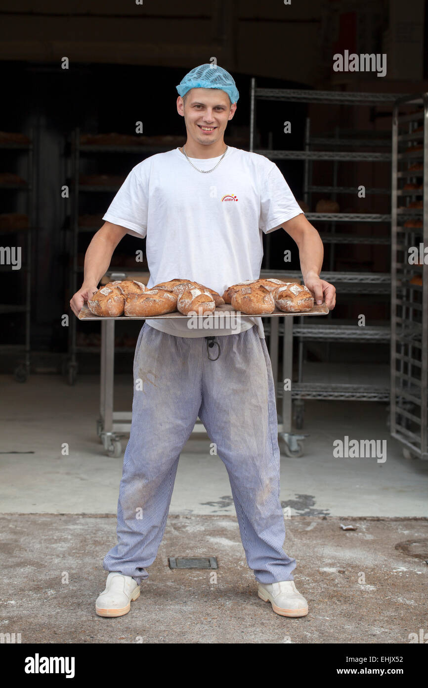 Baker holding a tray of freshly baked bread - Stock Image