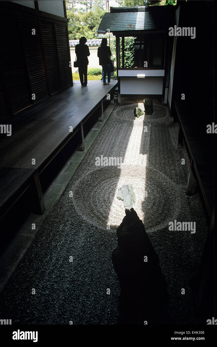 A pair of visitors hesitate for a moment while a sunbeam illuminates a Zen garden vignette in one of the sub temples. - Stock Image