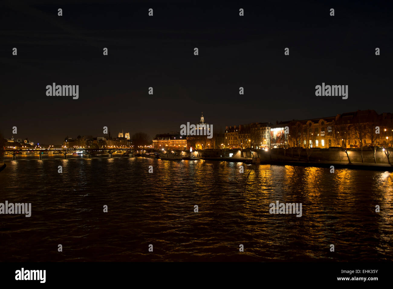 The Seine in Paris by night in winter, looking towards Rive Gauche - Stock Image